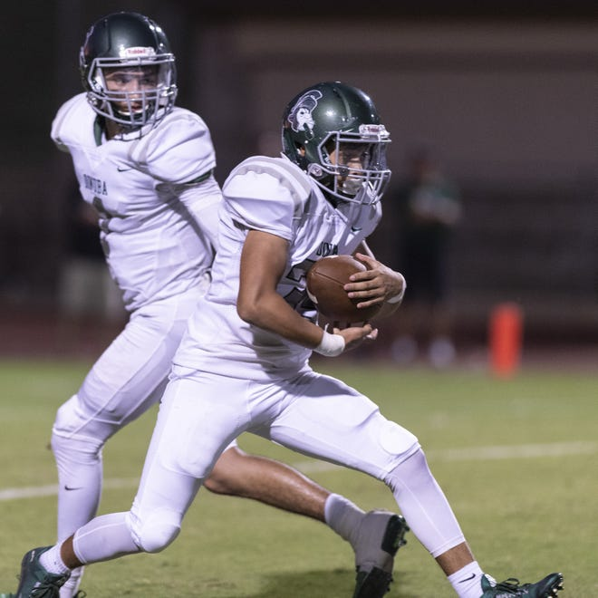 Dinuba quarterback Josh Magana, left, hands the ball of to an Emperors' running back against Redwood at Mineral King Bowl in a non-league football game on Friday, August 30, 2019. Dinuba will play Tulare Western on Friday in a Central Section Division II quarterfinal playoff game.