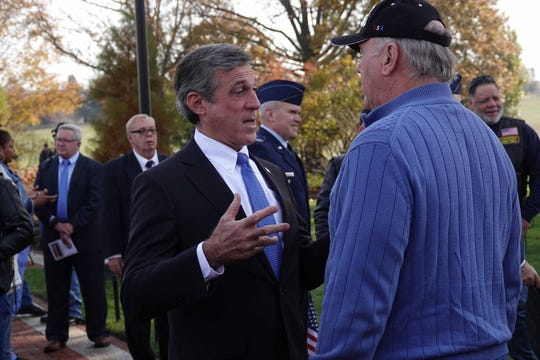 Gov. John Carney speaks with an attendee before the start of the annual Veterans Day ceremony at the War Memorial Plaza at the Delaware Memorial Bridge on Monday morning.