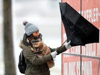 A woman walking the half mile from the Chicago Aquarium to the Adler Planetarium fights a stiff wind inverting her umbrella in the blowing snow off Lake Michigan, Monday, Nov. 11, 2019, in Chicago. (AP Photo/Charles Rex Arbogast) ORG XMIT: ILCA103