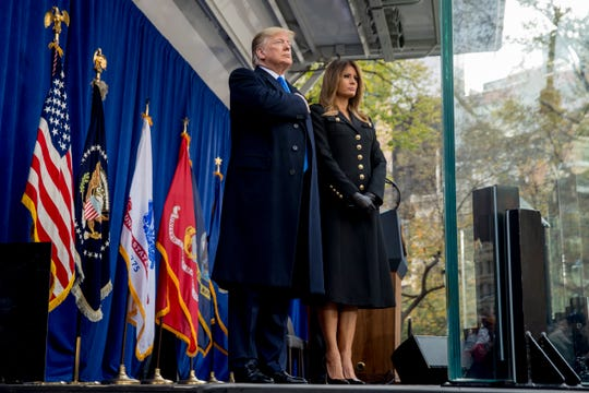 President Donald Trump and first lady Melania Trump on stage as taps are played during in a wreath laying ceremony at the New York City Veterans Day Parade at Madison Square Park in New York on Nov. 11, 2019.