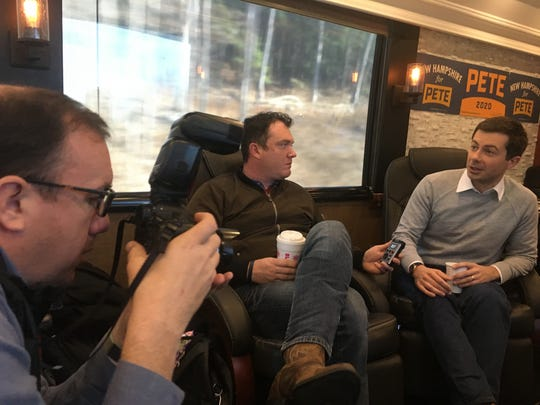 Democratic presidential hopeful Pete Buttigieg talks to reporters on his campaign bus during a four-day trip through New Hampshire.