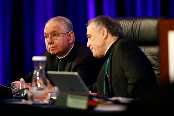 FILE - In this Monday, Nov. 12, 2018 file photo, Archbishop Jose Gomez of Los Angeles, vice president of the United States Conference of Catholic Bishops, left, sits with Cardinal Daniel DiNardo of the Archdiocese of Galveston-Houston, USCCB president, before the conference's annual fall meeting in Baltimore. Clergy sex abuse is once again on the agenda as U.S. Catholic bishops meet in November 2019 _ but so is a potentially historic milestone: Archbishop Gomez, an immigrant from Mexico, is widely expected to win election as the first Hispanic president of the bishops' national conference. (AP Photo/Patrick Semansky)