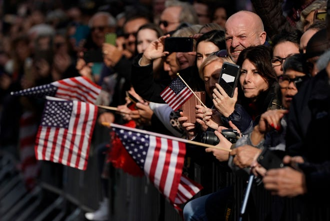 Spectators stand behind barricades along the Veterans Day Parade route in New York City.
