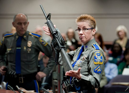 A Connecticut State Police detective in 2013 displayed a Bushmaster AR-15 rifle, the same make and model of gun used by Adam Lanza in the Sandy Hook Elementary School shooting, during a state legislative hearing in Hartford.