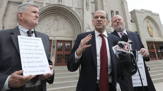 Mitchell Garabedian, Boston attorney, center, flanked by Robert Hoatson, former priest and founder of Road to Recovery, a victim's support organization, left, and James Faluszczak, survivor of abuse and former priest, right, hold a press conference on Diocese of Rochester priests accused of abuse outside the Diocese of Rochester in Rochester, New York, on Dec. 9, 2018.