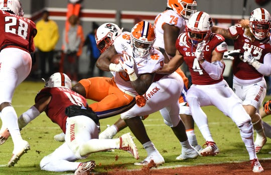 Clemson running back Travis Etienne scores a touchdown during the first half against North Carolina State Wolfpack at Carter-Finley Stadium.