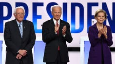 (FILES) In this file photo taken on October 15, 2019 (From L) Democratic presidential hopefuls Vermont Senator Bernie Sanders, former US Vice President Joe Biden and Massachusetts Senator Elizabeth Warren arrive onstage for the fourth Democratic primary debate of the 2020 presidential campaign season co-hosted by The New York Times and CNN at Otterbein University in Westerville, Ohio. (Photo by SAUL LOEB / AFP) (Photo by SAUL LOEB/AFP via Getty Images) ORG XMIT: Elizabeth ORIG FILE ID: AFP_1LU5MK