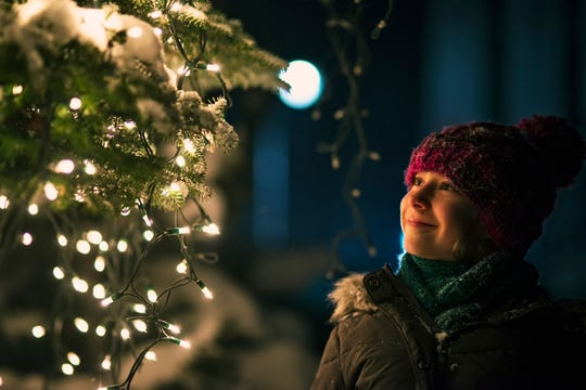File photo of a little girl looking at the illuminated Christmas tree outdoors during night.