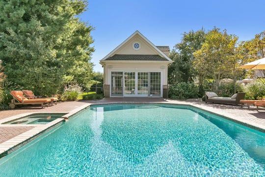 The backyard oasis offers an in-ground pool, sauna and lavish greenery.
