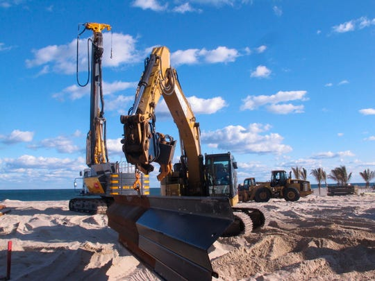 In this Nov. 8, 2019 photo, construction crews build a steel sea wall in Point Pleasant Beach, N.J. The privately owned Jenkinson's beach is spending $5 million to $6 million to build the wall instead of being required to let sand dunes be built on its beach. (AP Photo/Wayne Parry)