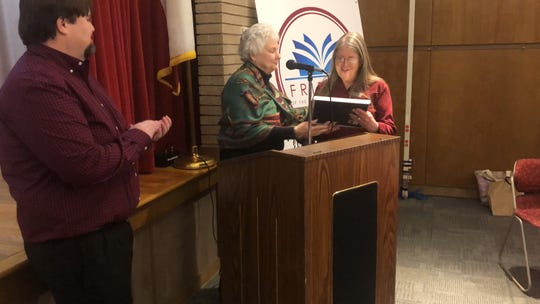 Lori Grumet, right, looks over a gift from the Friends of the Abilene Public Library, given to her Tuesday by outgoing Friends' President Judith Phaneuf. Grumet is retiring next week from the library system after five years in charge as director.