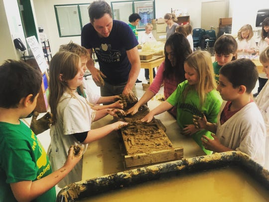 Artist Josh Copus works with students from Brush Creek Elementary to create bricks, some of which would ultimately be used for a piece featured in the Asheville Art Museum.