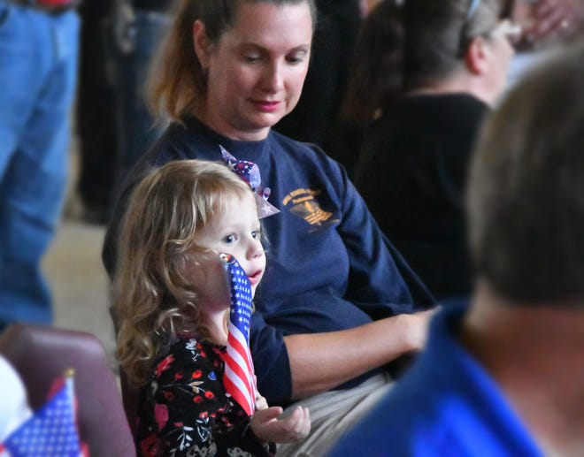 Violet Demko waves a small American flag while sitting with her mom, Wendy, during a sunset Veterans Day ceremony at Satellite Beach's City Hall. All vets were honored, with special recognition for the World War II veterans packing the front row.