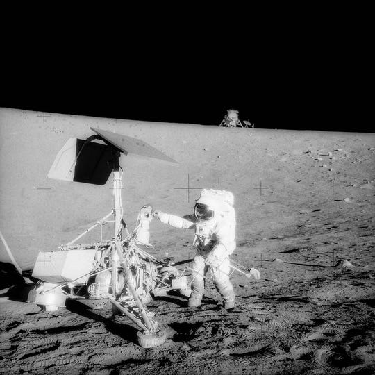Apollo 12 commander Pete Conrad stands with Surveyor 3, an unmanned U.S. lunar probe that landed on the moon in 1967.