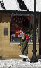 Diana Shroll shovels snow outside of her Sourth Sandusky Avenue business, Fit Fab Fun, on Tuesday morning.