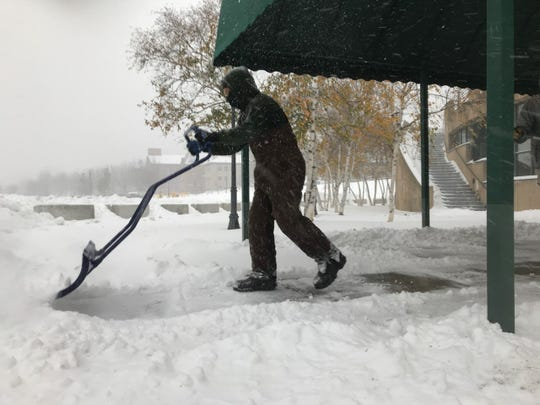 Trevon Smith, 20, of Ferrisburgh-based JFC Enterprises, shovels snow at Main Street Landing in Burlington at 8:15 a.m. on Nov. 12, 2019.