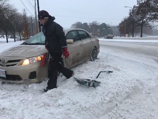 A man, who declined to identify himself, tries to free his car that got stuck on Main Street in Burlington on Nov. 12, 2019.