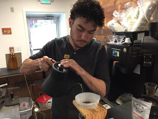 Daniel Gutierrez, an employee at Lost Monarch Coffee, works at the Public Market inside the Stone Mill in Middlebury on Nov. 11, 2019.