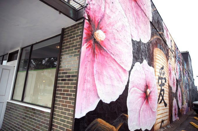 "A new mural by artist Jeremy Flores is located on the old Urbana Market and Deli building on Chaparral Street. The theme is a Japanese market. He has titled the piece ""The Dokyo Wall."""