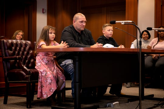 Michael McQueen sits between his step-grandchildren Caity, 5, and Carter, 9, who he is adopting on National Adoption Day at the Hamilton County Probate Court in downtown Cincinnati Friday, November 1, 2019.