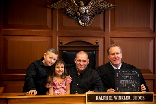 Michael McQueen poses for a photo with his adopted children Carter, 9, and Caity, 5, with Judge Ralph Winkler.