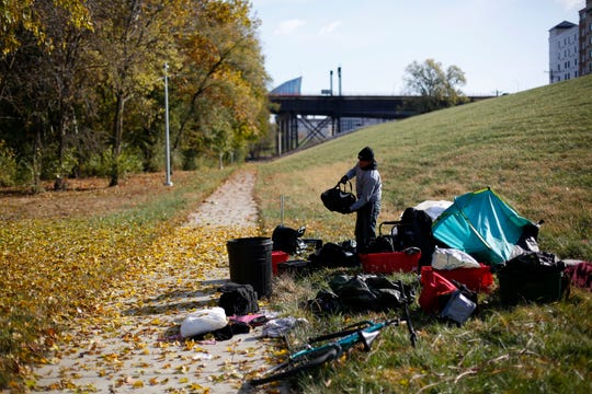 Aaron Hoskins, 25, packs up his camp and his belongings  near the banks of the Ohio River in Covington, Ky., on Friday, Nov. 8, 2019. Hoskins had been sleeping near the river's edge but was packing his camp and preparing to migrate toward Florence.