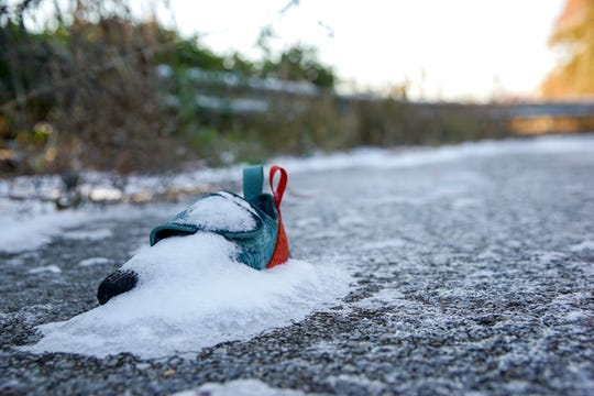 A tiny climbing shoe is covered with snow and sits in the parking lot at Kings Bluff in Clarksville, Tenn., on Tuesday, Nov. 12, 2019. | henrytaylor@theleafchronicle.com
