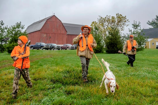 Nicholas, Brian, Gus, and Brian's dad, Gary, make their way towards the field while hunting at The Pheasant Farm in Grand Rapids on Sunday, Nov. 5, 2017. Hunting wildlife has long been ingrained in Michigan's culture, but it is currently on a decline across the state.