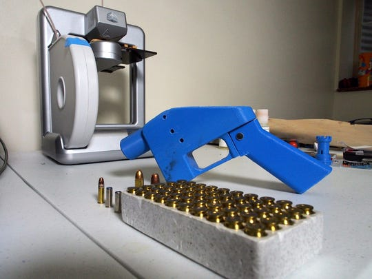In this file photo taken on July 17, 2013 a Liberator pistol appears next to the 3D printer on which its components were made in Hanover, Maryland.