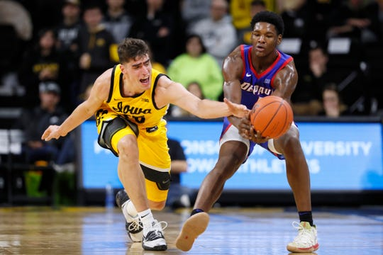 Iowa center Luka Garza, left, tries to steal the ball from DePaul forward Romeo Weems during the second half Monday. DePaul won 93-78.