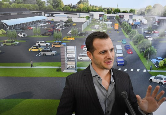 Rubicon Capital co-owner Manuel Ferraiuolo speaks in front of a rendering of  a proposed cannabis park and future shopping center in Pontiac, during a recent job fair.