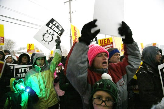 Teacher Amy Irvine, right, of Sterling Heights, with her son, Robert Irvine, 9, front, chants during the rally.