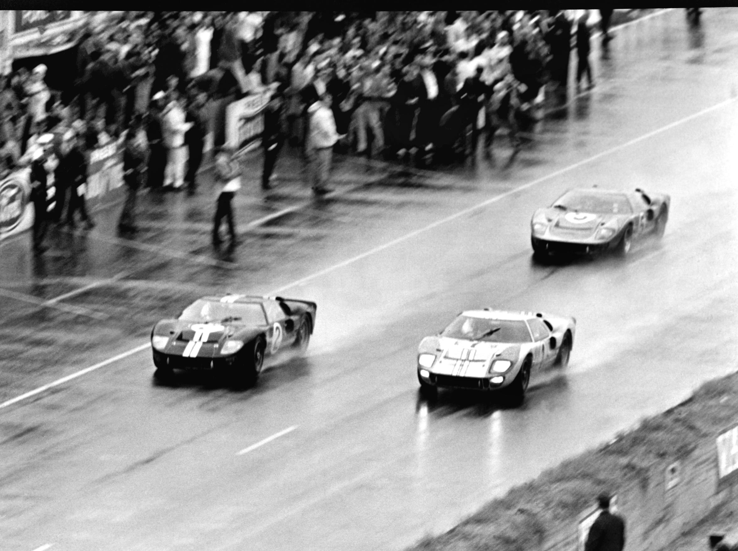 Three Ford GT40 MK II cars cross the finish line at Le Mans in 1966 in first, second and third place.