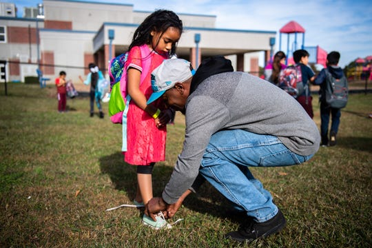 Derrick Little ties his the shoelaces of his daughter Neveah Little, 6, as he picks her up from Monaview Elementary School Friday, November 8, 2019.