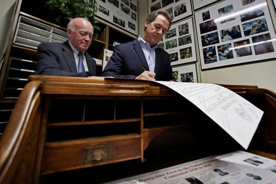 Democratic presidential candidate Montana Gov. Steve Bullock files to be placed on the New Hampshire primary ballot at the Statehouse,  Nov. 12, in Concord, N.H. At left is Secretary of State Bill Gardner. (AP Photo/Elise Amendola)