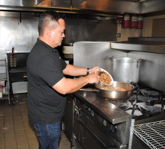 Chef Peter Duenas adds a riyenu basic ingredient Nov. 8, 2019, at Meskla Restaurant in Hagåtña. You won't find cubed, fried potatoes in most American bread-oriented stuffing.