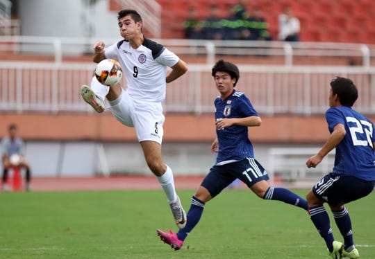 Guam's Jacob McDonald leaps to trap the ball against Japan on an opening day match of the AFC U19 Championship Qualifier Group J in Ho Chi Minh City, Vietnam, on Nov. 6. Guam fell to Japan 10-0.