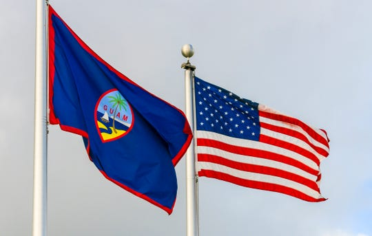 The Guam flag and U.S. flag fly in front of the Guam Congress Building in this Nov. 12 file photo.