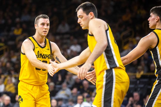 Iowa guard Connor McCaffery (left), getting high-fives from teammates Ryan Kriener and Luka Garza during a game last month, ranks fourth in the nation with 5.4 assists per turnover.