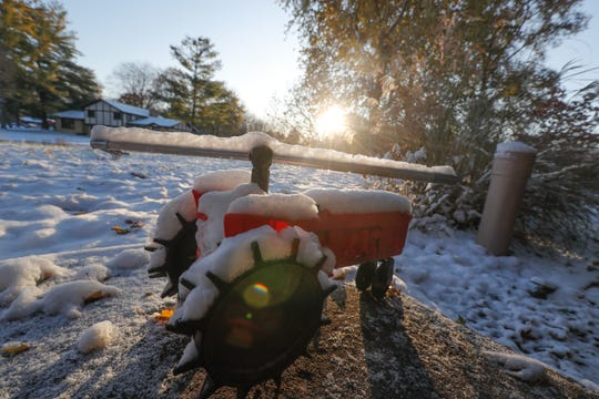 The sun rises on a frozen sprinkler on the north side of Indianapolis, on Tuesday, Nov. 12, 2019.
