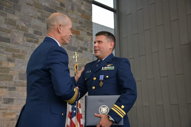 Lt. Cmdr. J.R. Carrillo, right, shakes hands with Coast Guard Adm. Charles Ray after receiving the Distinguished Flying Cross on Nov. 8, 2019, for his work as a helicopter pilot during Hurricane Harvey in 2017.