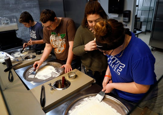 Cady Cox, second from right, watches as Hailey Gurewicz, right, Tyler Morin, second from left, and Cal Sims, left, practice making rolled ice cream Tuesday, Nov. 12, 2019, during a training session for employees at Extreme Creamery in Lancaster. The ice cream shop will open on Saturday.