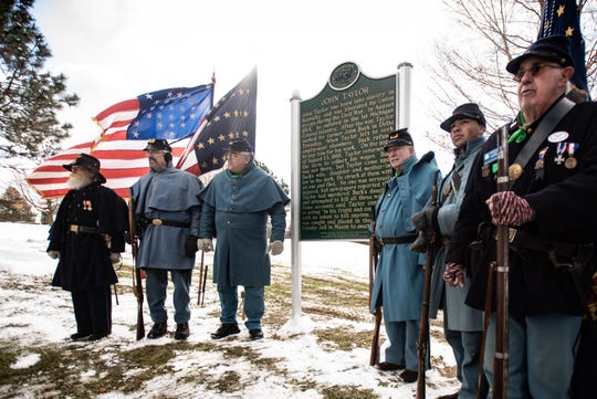 Members of the Sons of Union Veterans of the Civil War pose for a picture at John Taylor Memorial Park in Delhi Township, Tuesday, Nov. 12, 2019.  The park, formerly called Deadman's Hill, was dedicated as John Taylor Memorial Park during a ceremony where a marker was placed to honor the former slave and Union soldier. Taylor was a farmhand in the Mason area following the war. He was murdered by a mob after being accused of attacking a white family that owed him money. He was lynched in Mason in 1866. Though long thought to be buried at the site, his final burial site is unknown.