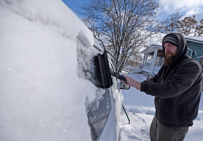Jake Kiser scrapes the snow and ice off the windows of his van early Tuesday after overnight snow fall.