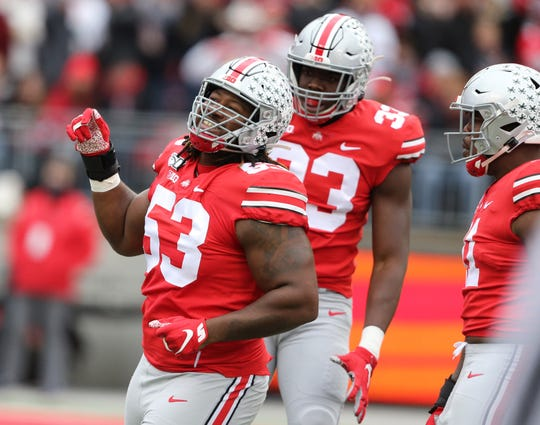 Absent their leader, Chase Young, Ohio State defensive linemen Davon Hamilton (53) and Zach Harrison (33) celebrate one of the Buckeyes' seven sacks in last Saturday's 73-14 rout of Maryland.
