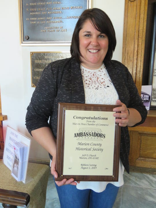 Brandi Wilson accepting a plaque from the Marion Area Chamber Of Commerce in honor of the 50th anniversary  of the Marion County Historical Society.