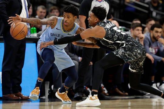 Memphis Grizzlies guard Ja Morant (12) and San Antonio Spurs guard Dejounte Murray (5) reach for a loose ball during the first half of an NBA basketball game, in San Antonio, Monday, Nov. 11, 2019. (AP Photo/Eric Gay)