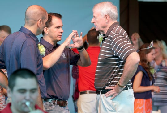 Then-Gov. Scott Walker chats with Milwaukee Mayor Tom Barrett before opening ceremonies of the 2017 Wisconsin State Fair. At left is West Allis Mayor Dan Devine. Walker and Barrett were on opposite sides of the debate over whether the city should be allowed to impose a residency requirement on its workers.