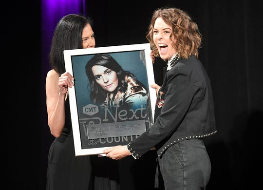 CMT's Leslie Fram, left, presents Brandi Carlile with the Impact Award the seventh annual Next Women of Country celebration at the CMA Theater at the Country Music Hall of Fame and Museum in Nashville on Tuesday, Nov. 12, 2019.