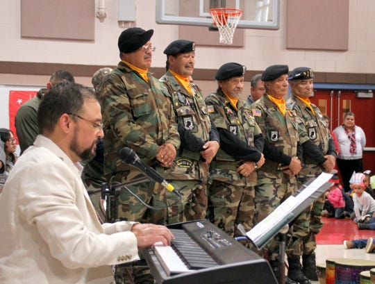 Brandon Perrault plays the keyboard while the Chapter 358 Vietnam, Afghanistan, Iraq Veterans Color Guard looks on.